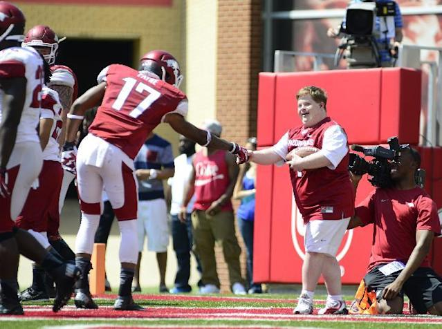 Arkansas Razorback fan Canaan Sandy is congratulated by Kendrick Payne (17) after scoring a touchdown on a play during their spring NCAA college football game, Saturday, April 26, 2014, in Fayetteville, Ark. (AP Photo/Sarah Bentham)