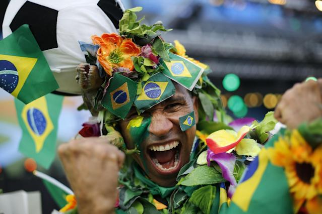 A Brazil soccer fan covered in flowers and his nation's flag cheers inside the FIFA Fan fest area before the start of the World Cup soccer game between Brazil and Croatia on Copacabana beach in Rio de Janeiro, Brazil, Thursday, June 12, 2014. (AP Photo/Silvia Izquierdo)