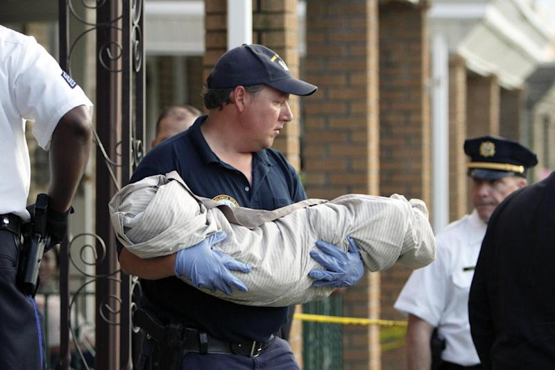 A crime scene unit member carries a body from a home in Northeast Philadelphia on Thursday May 24, 2012, where toddler twins were found dead in their home. Police say the 18-month-old boy and girl appear to have died of suffocation and the mother is in custody.  Police say their 41-year-old mother attempted to take her own life by slitting her wrists and they believe she gave some kind of prescription pills to her 4-year-old daughter. The 4-year-old girl is hospitalized. Information on her condition wasn't available. (AP Photo/Joseph Kaczmarek)