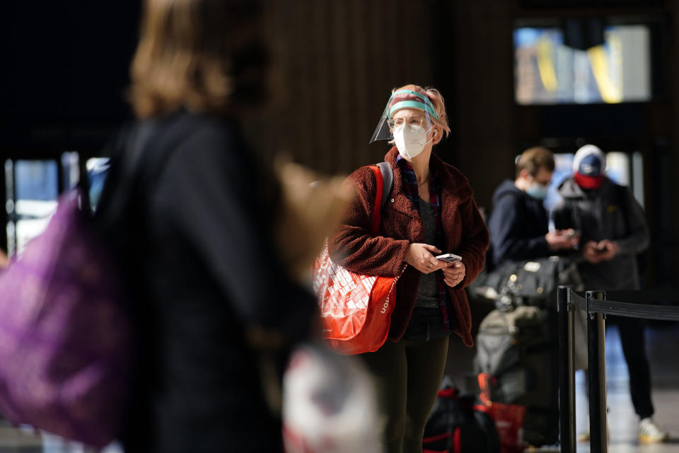 A woman waits in line for a train at the 30th Street Station ahead of the Thanksgiving holiday, Friday, Nov. 20, 2020, in Philadelphia. As governors and mayors grapple with an out-of-control pandemic, they are ratcheting up mask mandates and imposing restrictions on small indoor gatherings, which have been blamed for accelerating the spread of the coronavirus. (AP Photo/Matt Slocum)