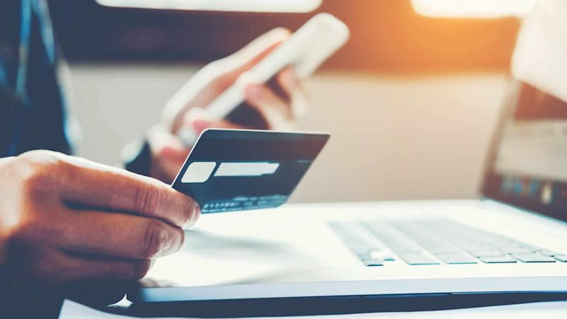 Online shopper holding credit card in front of laptop