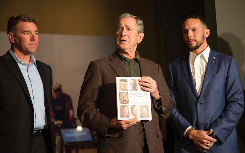 George W Bush holds up a copy of his