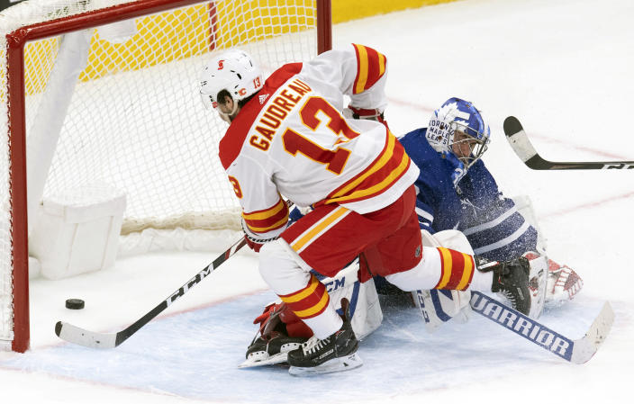 Calgary Flames' Johnny Gaudreau (13) scores the game winning goal on Toronto Maple Leafs goaltender David Rittich (33) in overtime of an NHL hockey game Tuesday, April 13, 2021 in Toronto. (Frank Gunn/Canadian Press via AP)