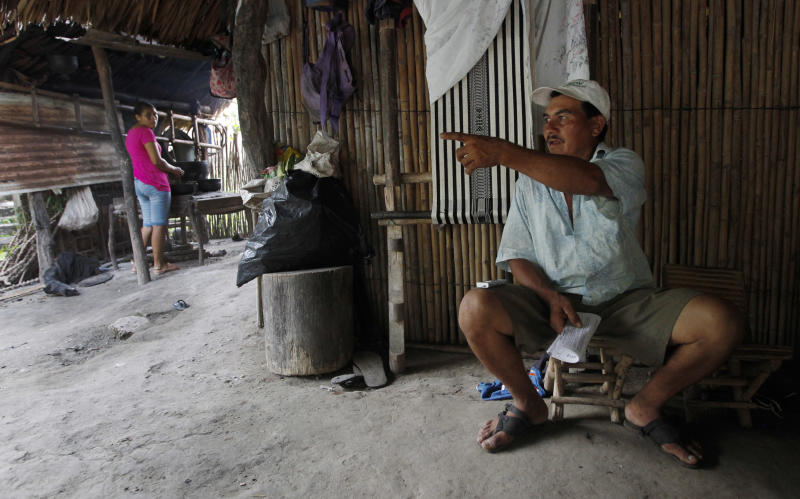 In this May 28, 2013 photo, Donaldo Ruiz speaks during an interview as his daughter Cenid Ruiz, background, left, prepares a meal at their home in Morroa, in Colombia's northwestern Sucre state. Ruiz and his relatives were among 40 families who abandoned their farm in Pechilin nearly a decade ago caught in the crossfire between leftist rebels, paramilitary groups and security forces. In April a court ordered that the land, that had gone through the hands of different owners before ending in the hands of a Venezuelan businessman, must return to the families. (AP Photo/Fernando Vergara)
