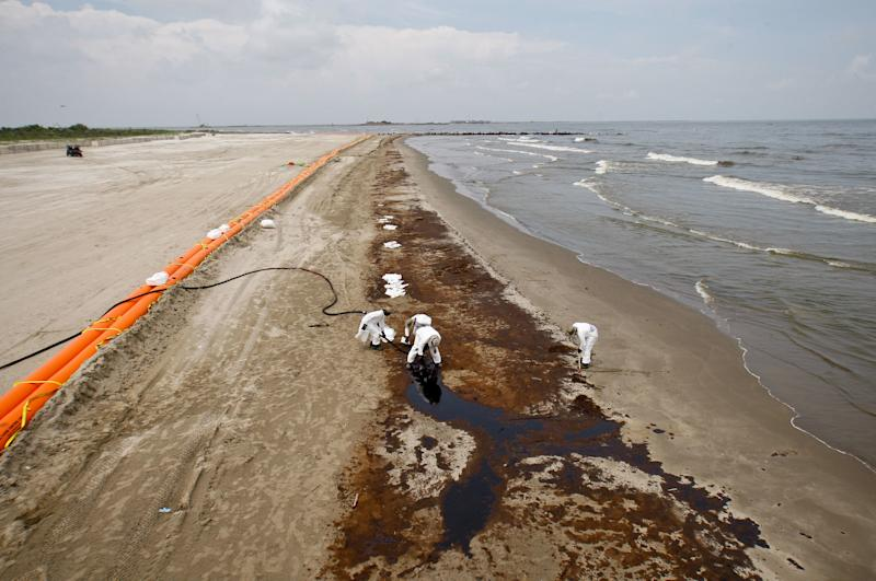 BP oil company contract workers remove oil that washed onto the beach at Grand Isle State Park in Louisiana on June 6, 2010. (Bloomberg via Getty Images)