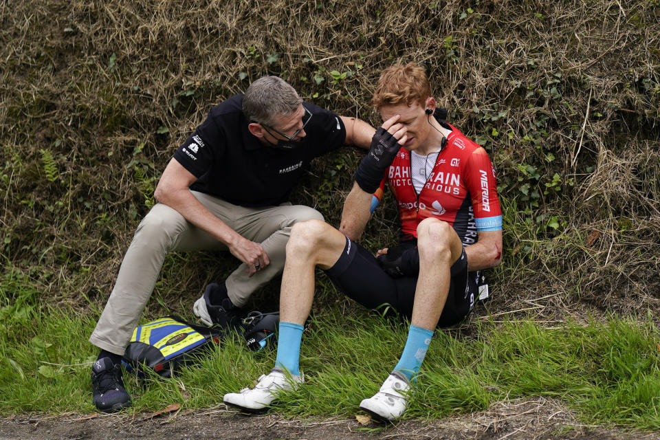 Australia's Jack Haig gets assistance from a team member after crashing during the third stage of the Tour de France cycling race over 182.9 kilometers (113.65 miles) with start in Lorient and finish in Pontivy, France, Monday, June 28, 2021. (AP Photo/Daniel Cole)