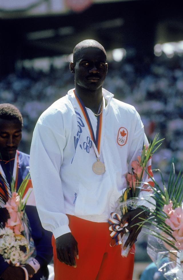 Canadian sprinter Ben Johnson on the winners podium with his gold medal after winning the 100 Metres event at Seoul Olympic Stadium during the Olympic Games in Seoul, South Korea, 24th September 1988. On the left is bronze medal winner Linford Christie of Great Britain. Johnson won the event in a world record time of 9.79 seconds, but was disqualified for doping, with Carl Lewis of the USA, taking the title. (Photo by Tony Duffy/Getty Images)