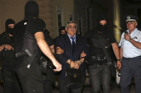 Extreme-right Golden Dawn party leader Michaloliakos is escorted by anti-terrorist police officers into a court in Athens