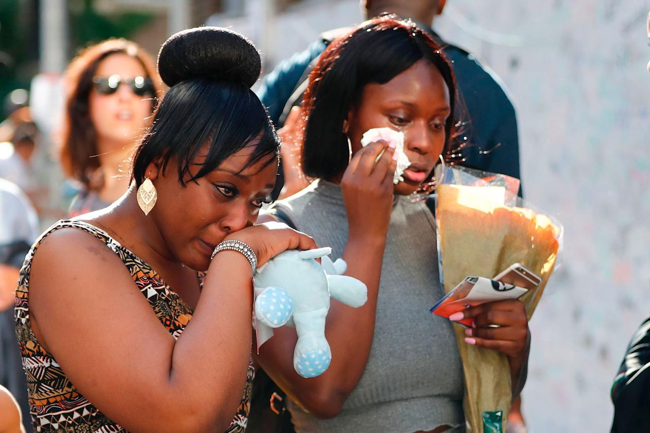 <p>Two women cry as they bring flowers, in the aftermath of the June 14 Grenfell Tower block fire, in Kensington, west London, on June 17, 2017. (Tolga Akmen/AFP/Getty Images) </p>