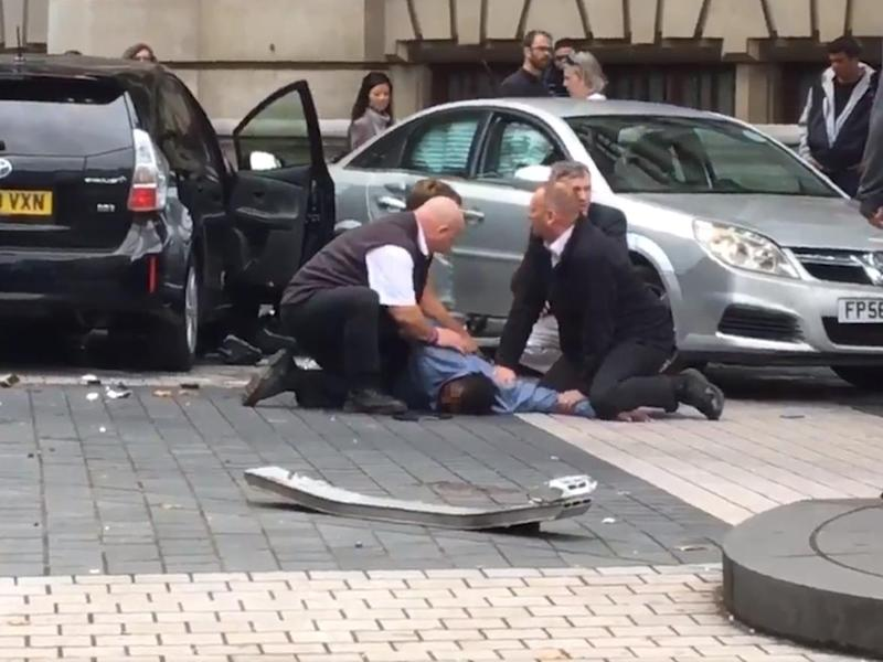 Police pin down a man, believed to be the driver, following the accident outside the museum: Patrick Greenfield