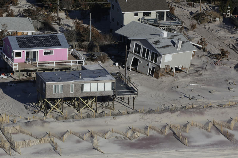 FILE - This Friday, Jan. 18, 2013 aerial file photo shows oceanfront homes on New York's Fire Island, damaged when Superstorm Sandy struck on Oct. 29, 2012. The seasonal return of the piping plover, an endangered bird species, will severely restrict truck access to the barrier island during cleanup efforts. (AP Photo/Mark Lennihan, File)