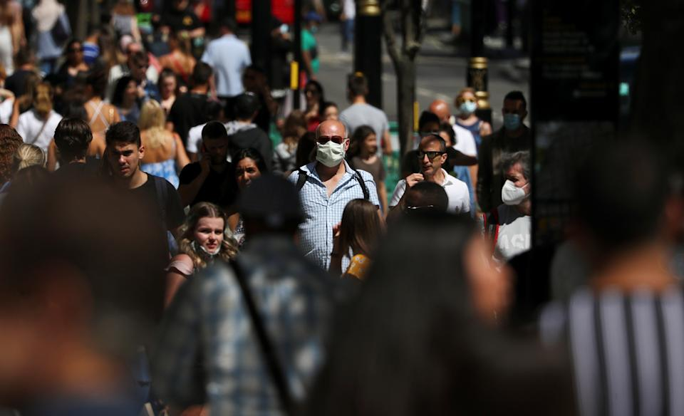 A man wearing a face mask is pictured among a crowd in Oxford Street, following the coronavirus disease (COVID-19) outbreak, in London, Britain, July 18, 2020. REUTERS/Simon Dawson