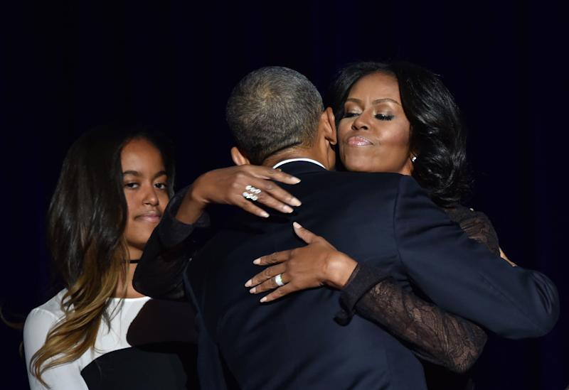 Michelle Obama hugs President Obama as daughter Malia looks on.