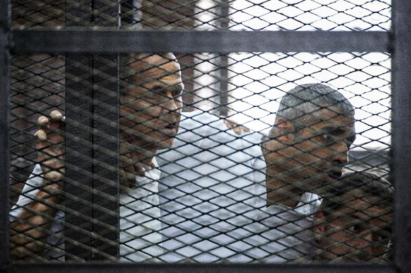 Al-Jazeera journalists Peter Greste (L), Mohamed Fadel Fahmy (C) and Baher Mohamed listen to the verdict from the defendants cage during their initial trial in June 2014 in Cairo