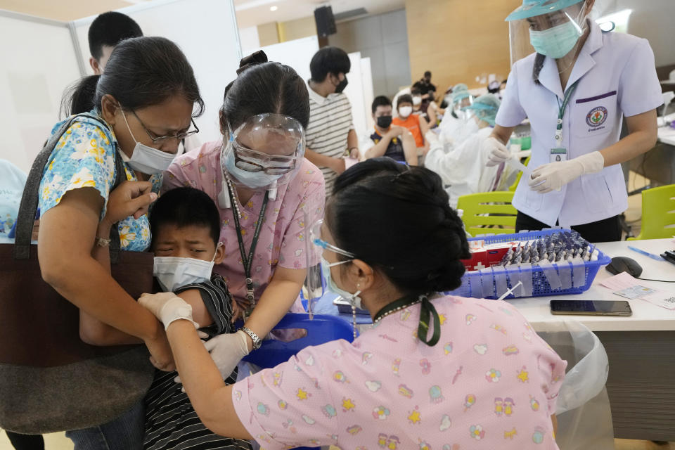 A mother tries to comfort her son refusing to get the Pfizer-BioNTech COVID-19 vaccine at a hospital in Bangkok, Thailand, Tuesday, Sept. 21, 2021. Bangkok Metropolitan Administration inoculated 12-18 year old students on Tuesday as part of its attempt to reopen on-site schools. (AP Photo/Sakchai Lalit)