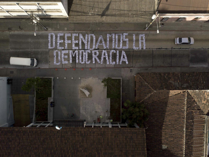 """Seen from above, a sign covering a street forms the Spanish phrase: """"We defend democracy,"""" made with photographs of the president and his cabinet, outside the Constitutional Court in Guatemala City, Wednesday, Jan. 9, 2019. Guatemala's highest court has blocked President Jimmy Morales' decision to unilaterally end the United Nations International Commission Against Impunity, CICIG. (AP Photo/Santiago Billy)"""