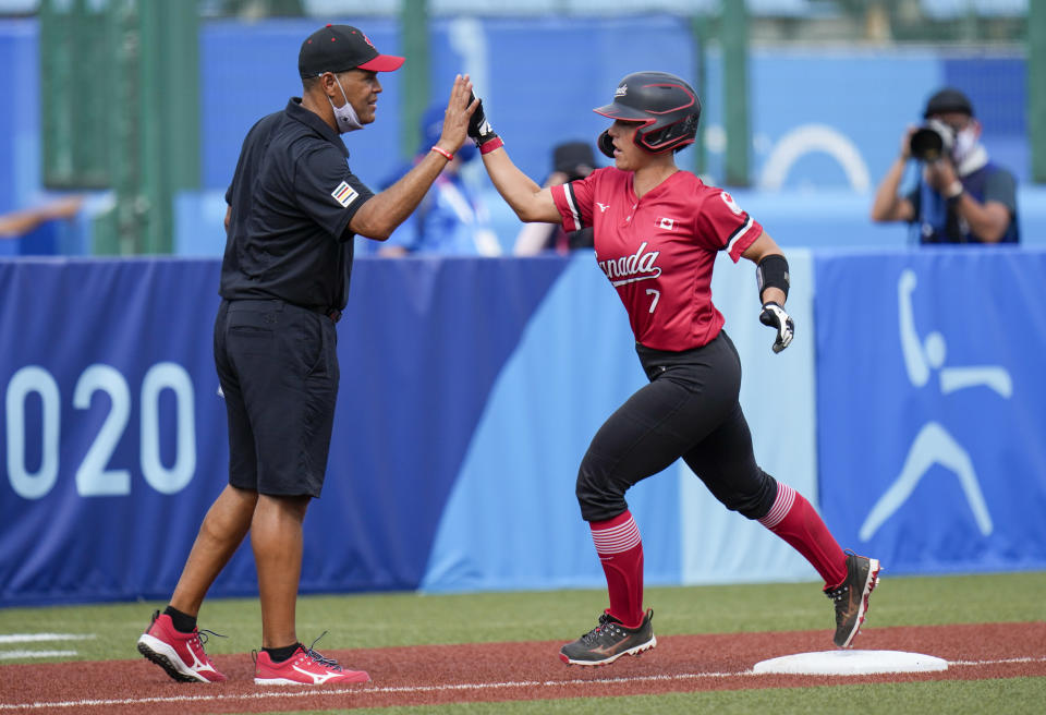 Canada's Jenn Salling is congratulated by head coach Mark Smith after scoring a home run during the softball game between Mexico and Canada at the 2020 Summer Olympics, Wednesday, July 21, 2021, in Fukushima , Japan. (AP Photo/Jae C. Hong)