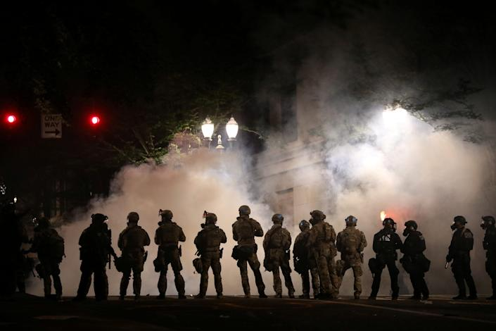 Federal law enforcement officers, deployed under the Trump administration's new executive order to protect federal monuments and buildings, face off with protesters against racial inequality and police violence in Portland, Oregon, U.S., July 21, 2020.