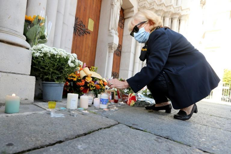 A woman lights a candle outside the Notre-Dame basilica in Nice after Thursday's attack