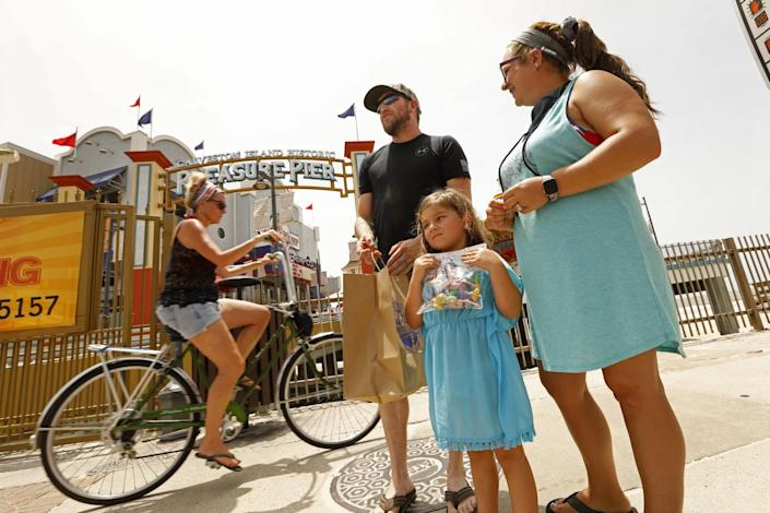 Jimmy, center, and Rachel Kinder, right, brought their daughter Arabella, 5, to the Pleasure Pier on Galveston Island.