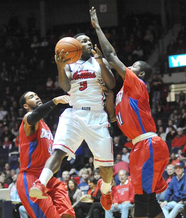 Mississippi's Derrick Millinghaus (3) scores between Dayton's Devon Scott (40) and Scoochie Smith (11) during an NCAA college basketball game in Oxford, Miss., Saturday, Jan. 4, 2014. (AP Photo/Oxford Eagle, Bruce Newman)