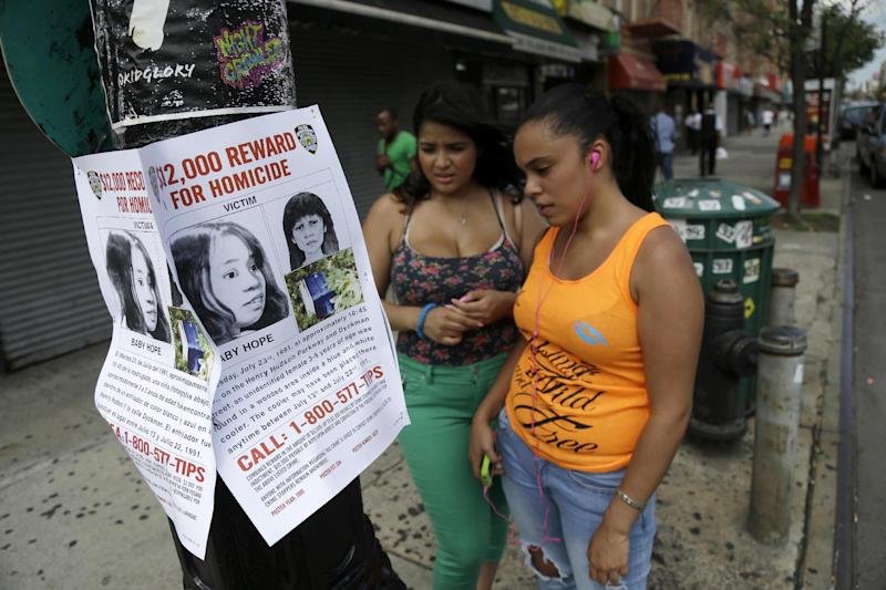 "In this Tuesday, July 23, 2013, photo passersby look at a poster soliciting information regarding an unidentified body near the site where the body was found in New York. More than two decades after the body of a child was found inside a cooler, the New York Police Department is seeking help identifying the girl dubbed ""Baby Hope."" On Tuesday, the 22nd anniversary of the discovery, police offered a $12,000 reward for any information leading to an arrest and conviction in the unsolved crime. (AP Photo/Seth Wenig)"