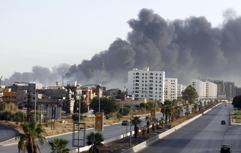Black smoke billows across the sky after a petrol depot was set ablaze during clashes between rival militias near Tripoli's international airport on August 13, 2014