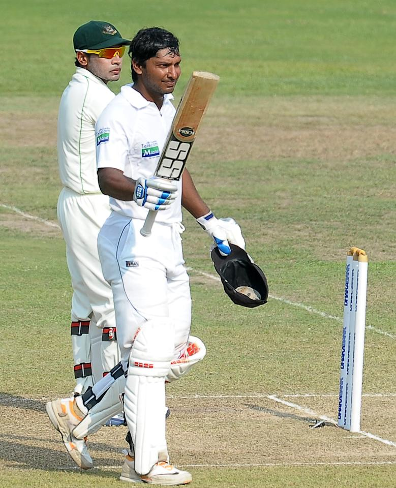 Sri Lanka's cricketer Kumar Sangakkara (R) raises his bat in celebration after scoring a century (100 runs) as Bangladeshi wicketkeeper and captain Mushfiqur Rahim look on during the second day of their second Test match between Sri Lanka and Bangladesh at the R. Premadasa Cricket Stadium in Colombo on March 17, 2013. AFP PHOTO/ LAKRUWAN WANNIARACHCHI