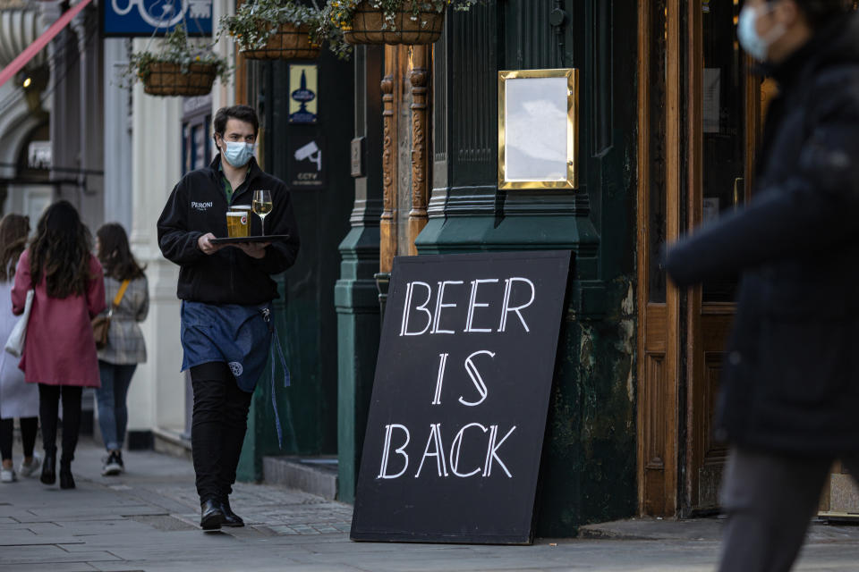 LONDON, ENGLAND - APRIL 16: A waiter at a pub carries a tray of drinks to a table on April 16, 2021 in London, England. Pubs and Restaurants are expecting good business tonight being the first Friday night after Coronavirus lockdown rules were relaxed to allow outside dining and drinking. (Photo by Rob Pinney/Getty Images)