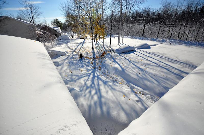 A man makes his way through nearly five feet of snow on November 19, 2014 in the Lakeview neighborhood of Buffalo, New York (AFP Photo/John Normile)