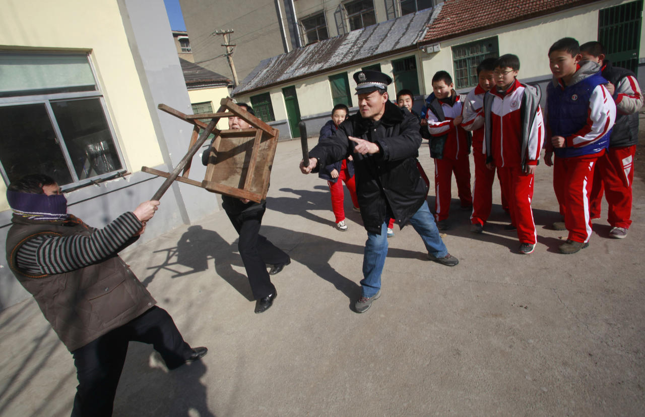 Students stand behind as a policeman and a teacher try to defend them against an intruder during an anti-violence exercise at a primary school in Jinan, Shandong province, December 18, 2012. The exercise was held four days after last Friday's knife attack at a primary school in Henan province, leaving more than 20 children and an elderly villager injured. Picture taken December 18, 2012. REUTERS/China Daily (CHINA - Tags: CRIME LAW EDUCATION) CHINA OUT. NO COMMERCIAL OR EDITORIAL SALES IN CHINA