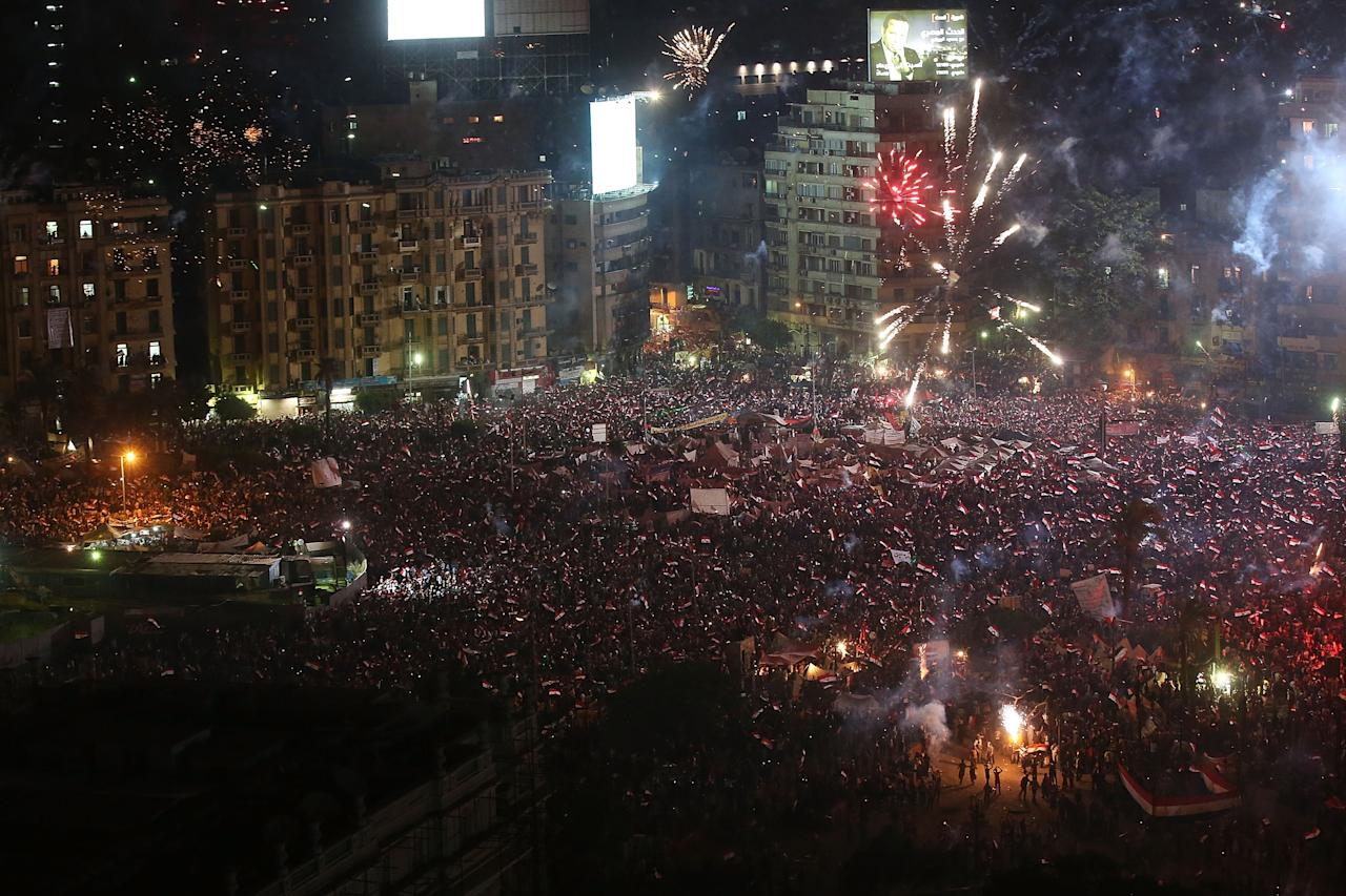 CAIRO, EGYPT - JULY 03: Fireworks and shouts of joy emanate from Tahrir Square after a broadcast by the head of the Egyptian military confirming that they will temporarily be taking over from the country's first democratically elected president Mohammed Morsi on July 3, 2013 in Cairo, Egypt. As unrest spreads throughout the country, at least 23 people were killed in Cairo on Tuesday and over 200 others were injured. It has been reported that the military has taken over the state television. (Photo by Spencer Platt/Getty Images)