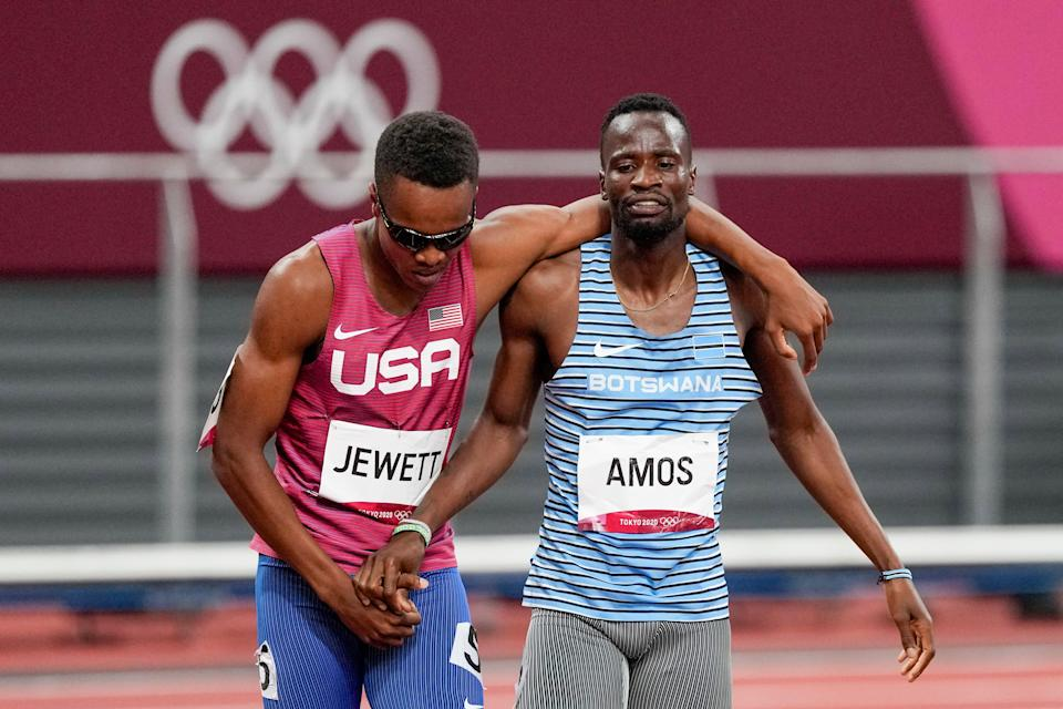The USA's Isaiah Jewett, left, and Botswana's Nijel Amos, right, shake hands after falling in the men's 800-meter semifinal at the Tokyo Olympics.