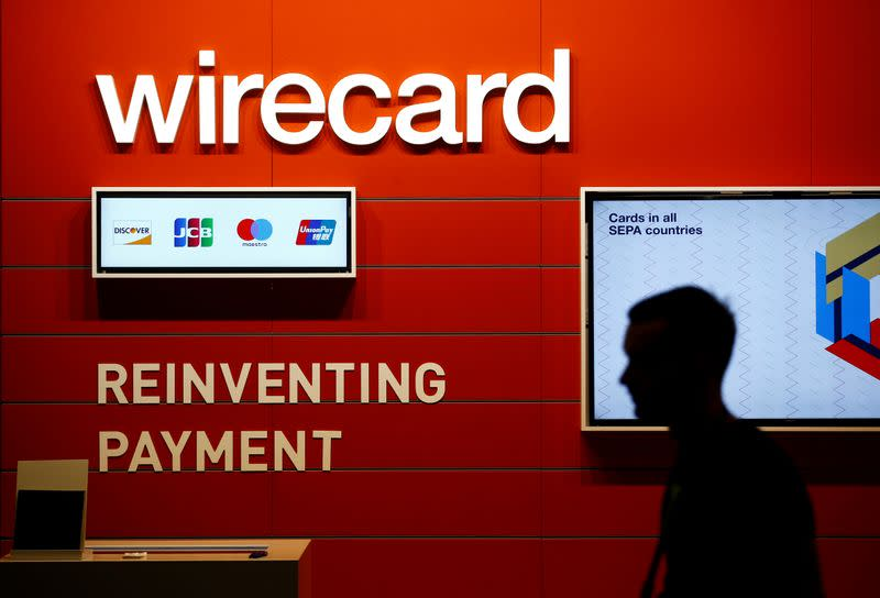 FILE PHOTO: A man walks past the Wirecard booth at the computer games fair Gamescom in Cologne, Germany