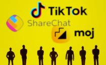 Small toy figures are seen in front of displayed TikTok, ShareChat and Moj logo in this illustration taken