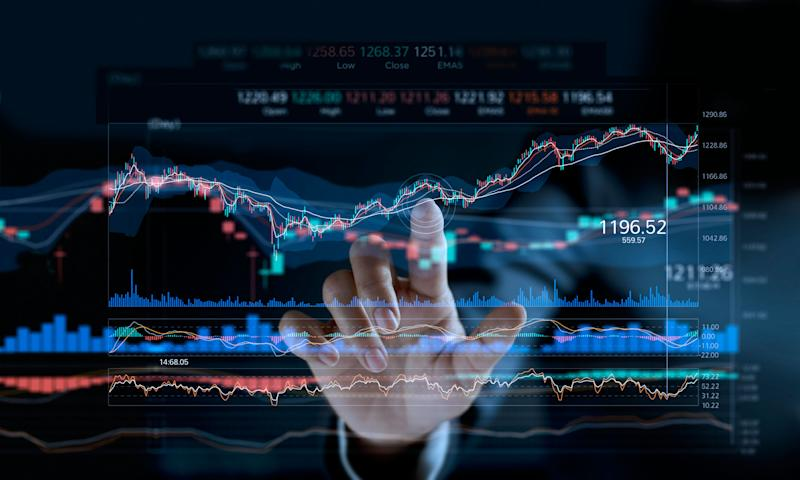 A person pointing to a stock market graph on a digital display