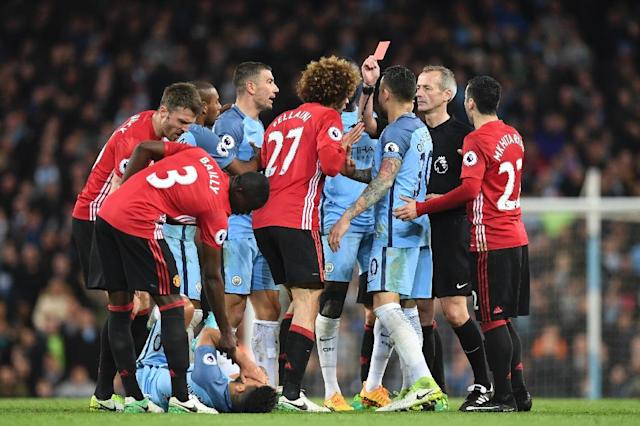 Referee Martin Atkinson (2R) shows the red card to send Manchester United's midfielder Marouane Fellaini (C) off after an altercation with Manchester City's striker Sergio Aguero (3L floor) during the Premier League football match April 27, 2017 (AFP Photo/Paul ELLIS)