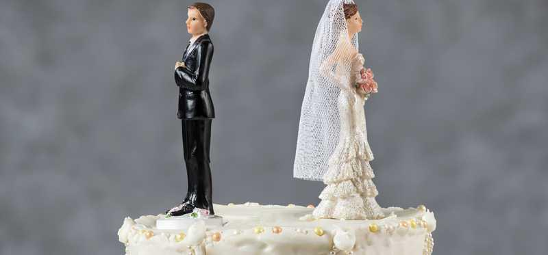Bride and groom cake toppers with their backs turned to each other.