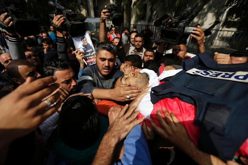 Mourners and journalists carry the body of Palestinian journalist Yasser Murtaja, during his funeral in Gaza City on Saturday