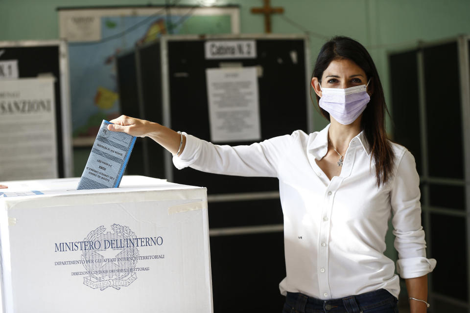 Rome Mayor Virgina Raggi poses for photographers as she casts her ballot at a polling station, in Rome, Sunday, Oct. 3, 2021. Millions of people in Italy started voting Sunday for new mayors, including in Rome and Milan, in an election widely seen as a test of political alliances before nationwide balloting just over a year away. (Cecilia Fabiano/LaPresse via AP)