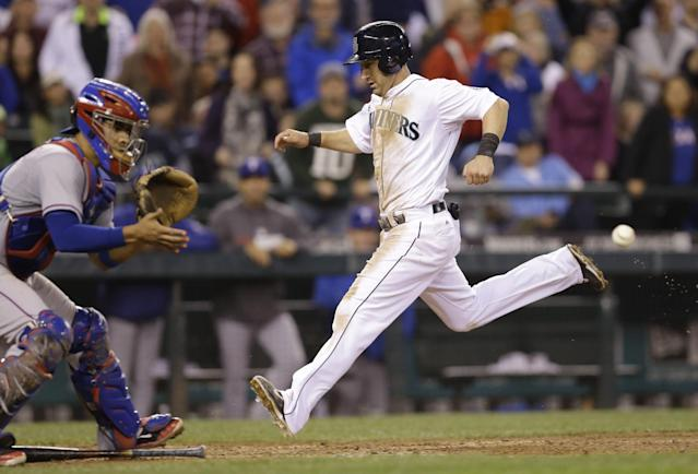 Seattle Mariners' Willie Bloomquist, right, beats the throw to Texas Rangers catcher Robinson Chirinos as he scores in the seventh inning of a baseball game Saturday, June 14, 2014, in Seattle. (AP Photo/Elaine Thompson)