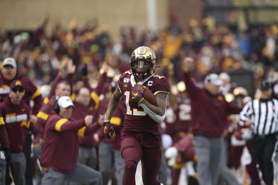 FILE - In this Nov. 9, 2019, file photo, Minnesota wide receiver Rashod Bateman (13) runs the ball down the field for a touchdown against Penn State during an NCAA college football game, in Minneapolis. Bateman initially opted out of the season on Aug. 4, citing concerns about playing amid the coronavirus pandemic, instead signing with an agent and focusing on the NFL draft. But he changed his mind when the Big Ten returned Sept. 16 with daily testing and earned special reinstatement from the NCAA. (AP Photo/Stacy Bengs, File)