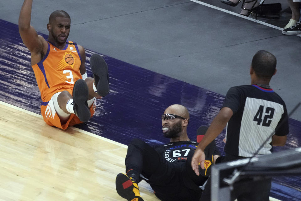 Phoenix Suns guard Chris Paul (3) reacts after getting knocked to the floor by New York Knicks center Taj Gibson (67) during the second half of an NBA basketball game Friday, May 7, 2021, in Phoenix. (AP Photo/Rick Scuteri)