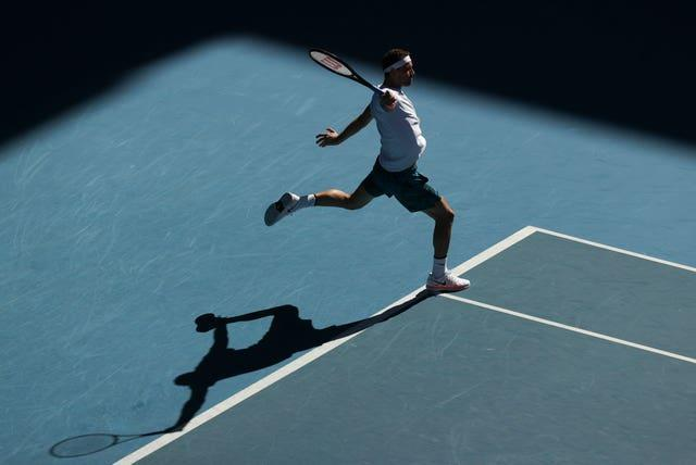 The sun shines on Grigor Dimitrov as he hits a one-handed backhand