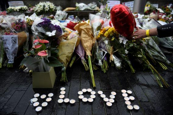 A person lays a floral tribute near the scene of the London Bridge attack