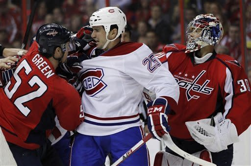 Montreal Canadiens right wing Brad Staubitz (25) argues with Washington Capitals defenseman Mike Green (52) and Washington Capitals goalie Michal Neuvirth (30) during the second period of an NHL hockey game on Saturday, March 31, 2012 in Washington. (AP Photo/Evan Vucci)