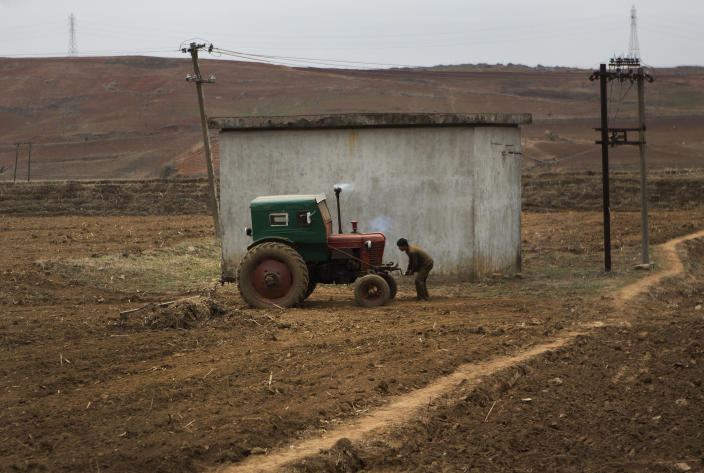 In this Thursday, May 23, 2013 photo, a North Korea farmer bank starts a tractor in a field along the highway between Pyongyang and Kaesong. Farmers in North Korea have confirmed that they have begun carrying out new economic policies designed to boost productivity by giving managers and workers financial incentives. Some foreign analysts say the moves are reminiscent of early reform in China in the late 1970s. (AP Photo/David Guttenfelder)