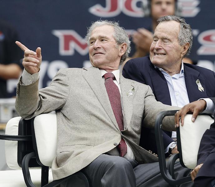 Former US Presidents George W. Bush (L) and George H.W. Bush at Reliant Stadium on November 17, 2013 in Houston (AFP Photo/Bob Levey)