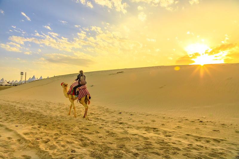 Desert safari in Qatar. Traveler man ride a camel on sand dunes of beach at Khor al Udaid in Persian Gulf. Tourist enjoys camel ride at sunset sunrays, a popular tour in Middle East, Arabian Peninsula