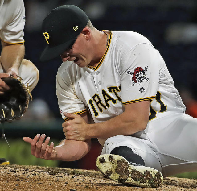 Pittsburgh Pirates relief pitcher Nick Burdi holds his right arm after delivering a pitch during the eighth inning of a baseball game against the Arizona Diamondbacks in Pittsburgh, Monday, April 22, 2019. Burdi left the game with a team trainer. The Diamondbacks won 12-4. (AP Photo/Gene J. Puskar)